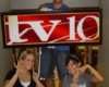 Students help install a sign with TV-10s new logo.
